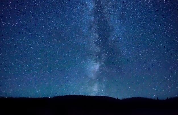Night dark blue sky with many stars and milky way galaxy above a mountain