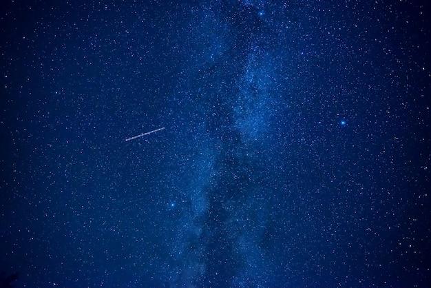 Ночное темно-синее небо с множеством звезд галактики млечный путь и летающим спутником
