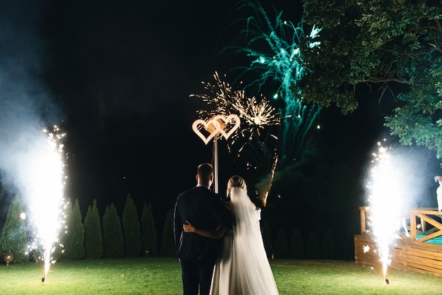 Ночной вечер - это фон. общий план роста. на свадьбе молодожены видят в небе красивый салют.