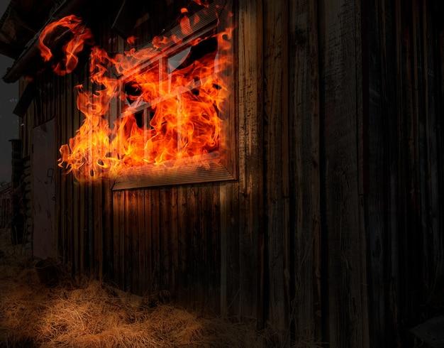 木造住宅での夜の火。木造住宅の窓からの炎。火の家。悪夢