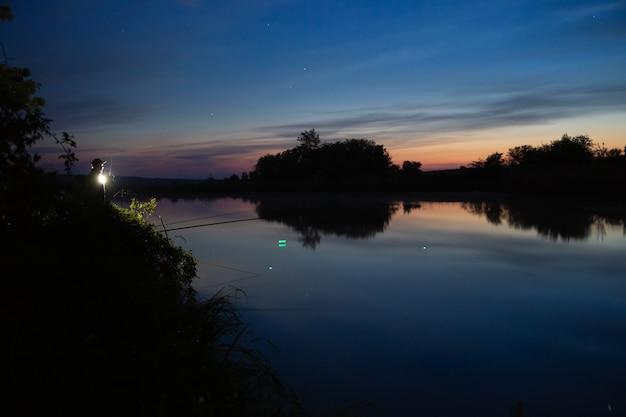 Ночная рыбалка, рыбак с удочкой на берегу озера.