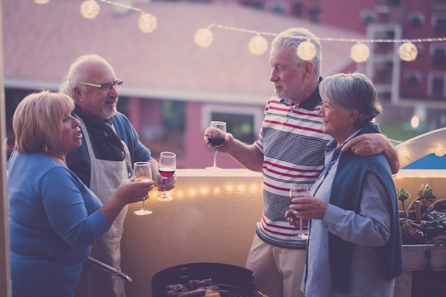 Night friends people celenbrate together with red and white wine having fun together - city view on terrace - barbecue and friendship for adult senior men and women - caucasian matures couples