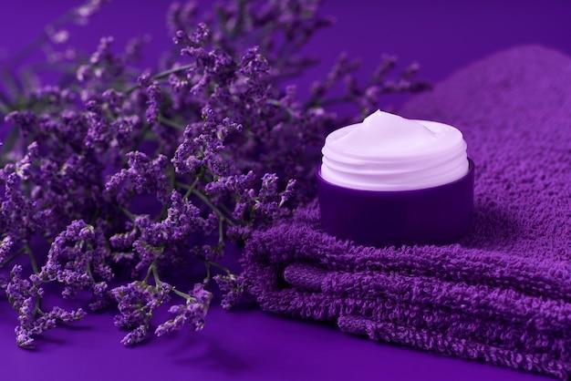 보라색 배경에 수건이 있는 플라스틱 병에 야간 치유 허브 화장품 크림, 위생적인 피부 관리 제품 또는 편안한 메이크업 마스크.