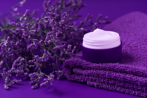 Night healing herbal cosmetic cream, hygienic skin care product or relaxing makeup mask in a plastic jar with a towel on a purple background.