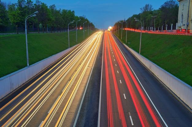 자동차 조명이 있는 야간 고속도로. 속도 트래픽이 있는 도로에 노란색과 빨간색 표시등이 있습니다. 긴 노출 추상 도시 배경