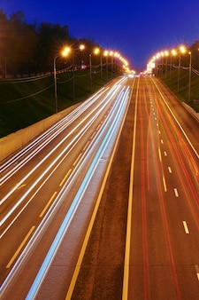 Night highway road with cars lights. yellow and red light trail on the road with speed trafic. long exposure abstract urban background