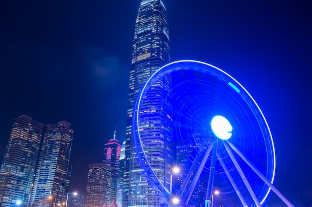 Night in hong kong city. large ferris wheel with skyscrapers