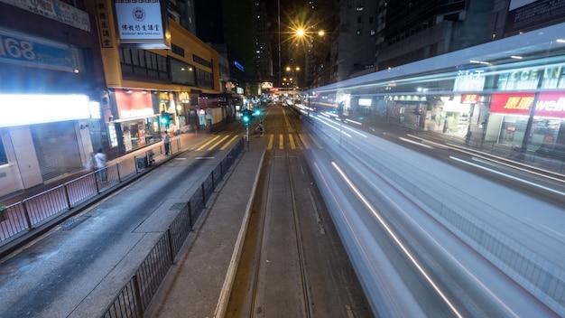 철도와 움직이는 전차와 함께 밤 홍콩 거리