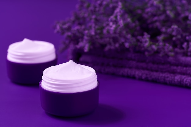 Night hygienic cream skincare product  in purple plastic jar with towel on table. skin cleansing cosmetic cream or vitamin spa lotion, a natural organic herbal anti-wrinkle moisturizer.
