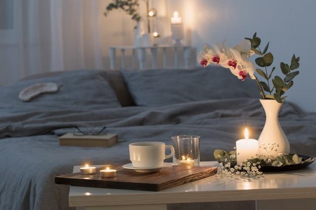 花と非常に熱い蝋燭が付いている寝室の夜のインテリア