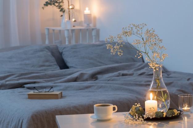 Ночной интерьер спальни с цветами и зажженными свечами