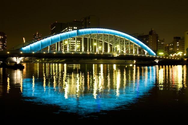 밤 철 다리와 강에 반사