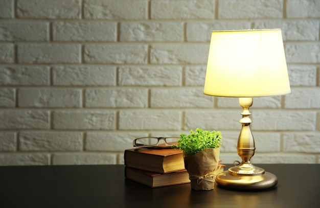 常夜灯と白いレンガの壁の背景の机の上の本