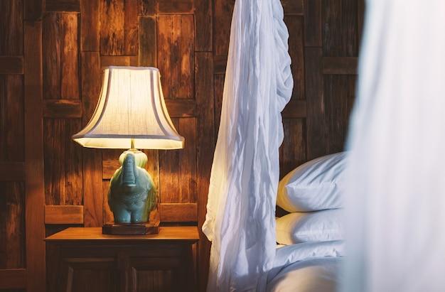 Ночник возле кровати с белыми льняными балдахинами в деревянном интерьере в отеле