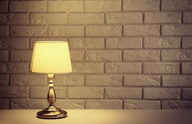 白いレンガの壁の背景に机の上の常夜灯