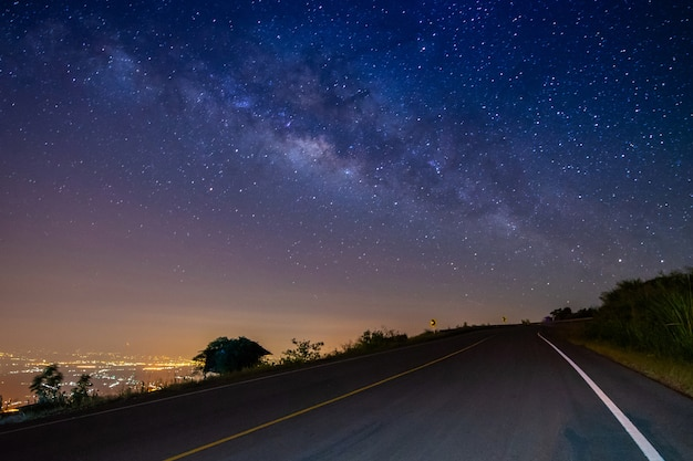 Night landscape road on mountain and milky way galaxy background