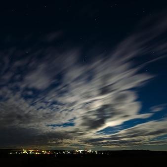 Ночной пейзаж при полной луне. звездное небо с облаками.