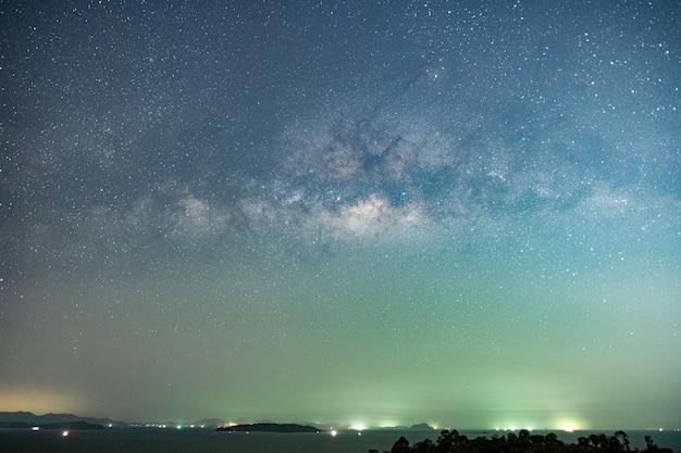 산에서 다채로운 은하수와 녹색 불빛이 있는 밤 풍경 여름에 언덕이 있는 다채로운 별이 빛나는 하늘. 배경을 위한 공간 복사 자연과 여행 모험 개념으로 이동합니다.