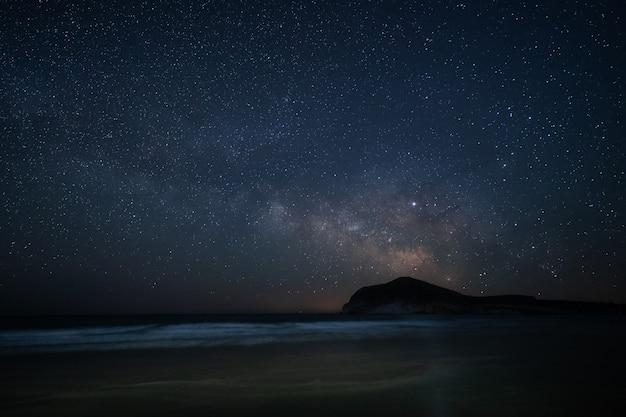 Ночной пейзаж с млечного пути от пляжа дженовезе. природный парк кабо де гата. андалусия. испания.