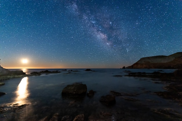 Night landscape with moon and milky way on the coast of the escullos. natural park of cabo de gata. spain.