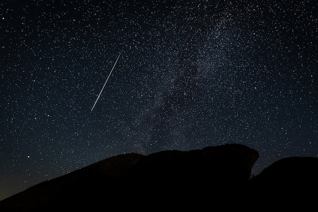 Night landscape with perseid meteor in barruecos. spain.