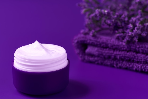 Night organic face cream or lotion, nature cosmetic to moisturize the skin with towel and purple flowers in the background, copy space for text.