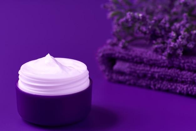 야간 유기농 페이스 크림 또는 로션, 수건과 보라색 꽃으로 피부를 보습하는 천연 화장품, 텍스트를 위한 복사 공간.