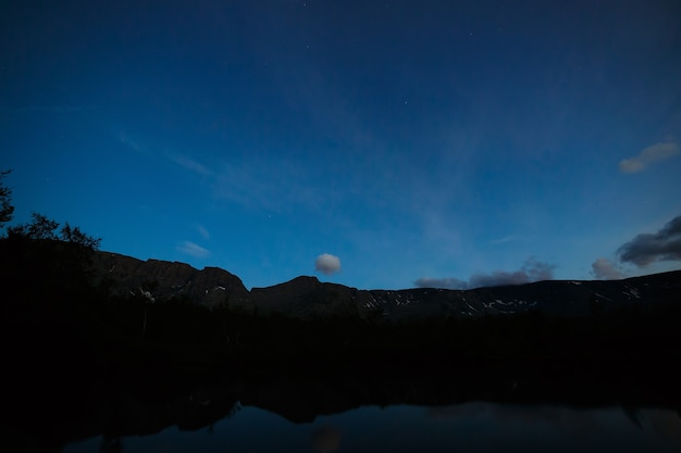 ヒービヌィの山々が見える夜のパノラマ、空が湖に映る小さなヴディヤヴル。ロシア、コラ半島。