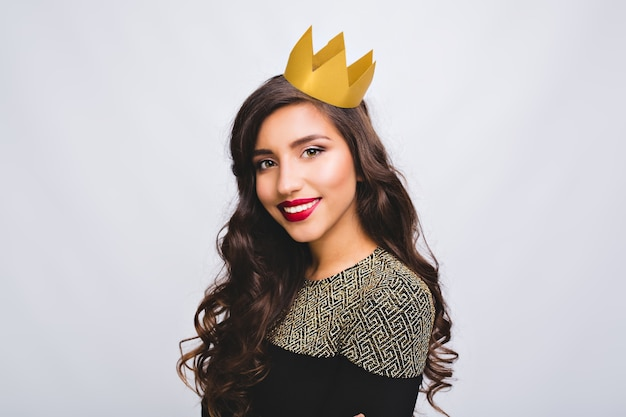 夜のパーティー、誕生日、新年のお祝い。ホワイトスペースの黄色い王冠の長いブルネットの巻き毛の肖像画うれしそうなかわいい女の子