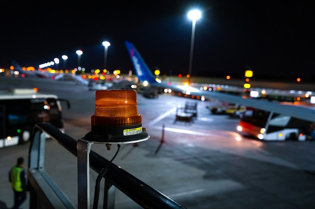 Night photo, close-up, yellow beacon to attract attention to the large-sized airport equipment. blurred aircraft parking