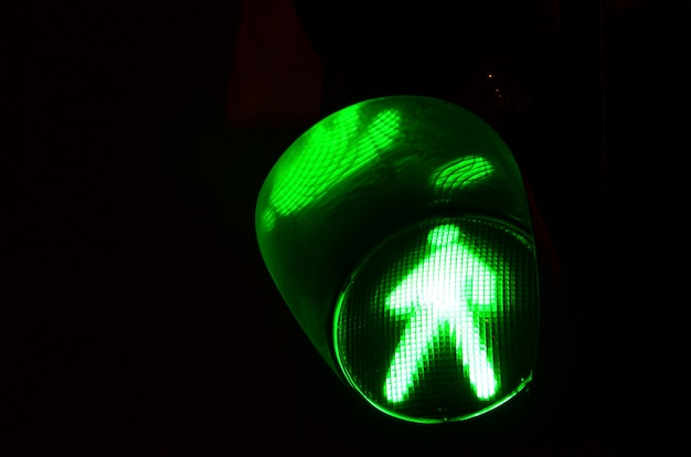 Night photo of a traffic light for pedestrians, which lights up in green