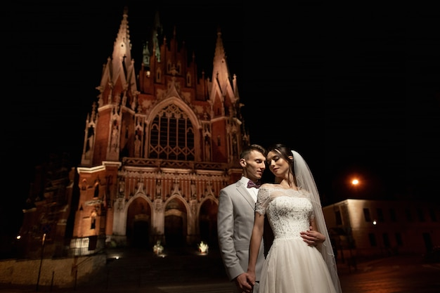 Night photosession of wedding couple in krakow, newlyweds walk around the church