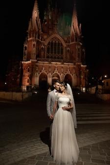 Night photosession of wedding couple in krakow. newlyweds walk around the church