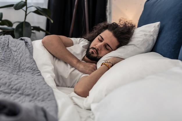 At night. pleasant brunette man lying in the bed while having a rest at home