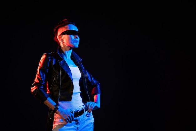 가죽 재킷을 입은 여성 네온 불빛 긍정적인 태도 자신감 있는 행복한 여성의 야간 초상화...