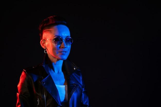 Ночной портрет женщины неоновый свет положительное отношение уверенная счастливая женщина в кожаной куртке и ...