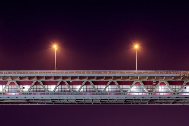 Освещение ночного скоростного моста. минималистичный свет, копия пространства. два фонарных столба с желтым освещением, фиолетовым синим фоном неба сумерек.