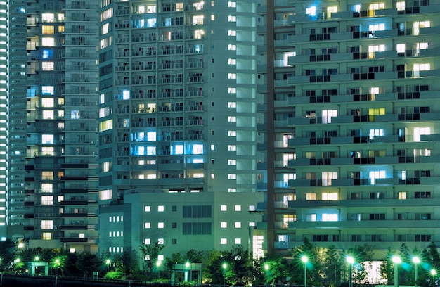 Night residential building with many windows illuminated, with street lights below