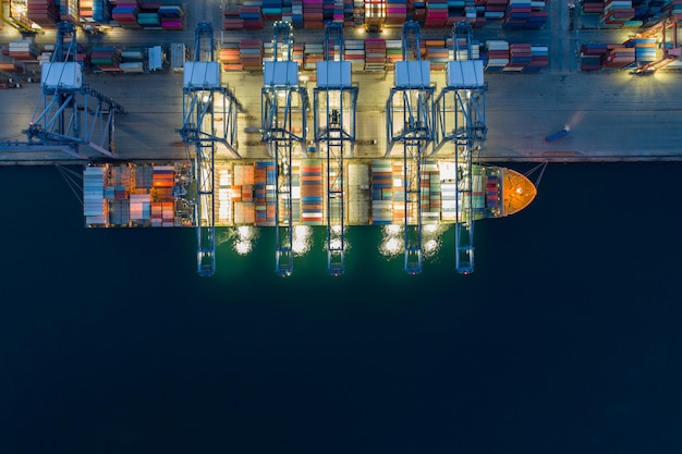 Night scene aerial view sea port container cargo loading ship in import export business logistic. freight transportation. shipping business logistic. trade port and shipping cargo to harbor.