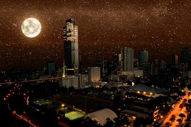 Night scene of modern city with glowing lights and stars