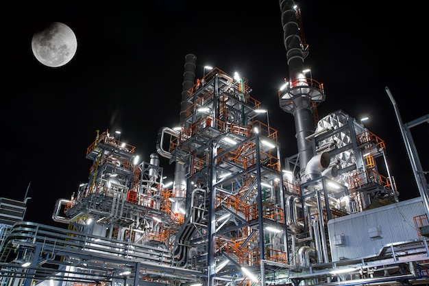 황혼의 보름달에 파이프 정제소가 있는 중화학 공업 공장의 세부 야경