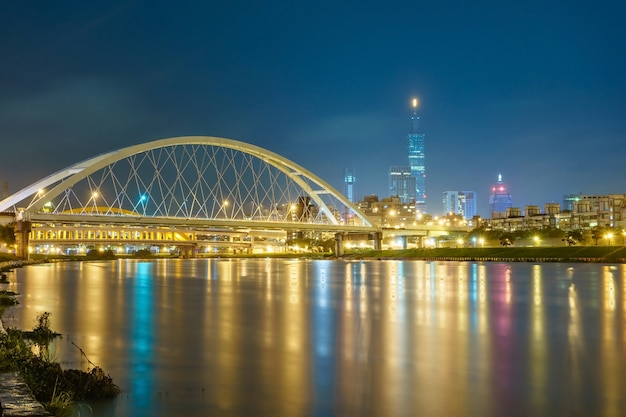 Night scenery of taipei city with beautiful reflections of skyscrapers & bridges at dusk.