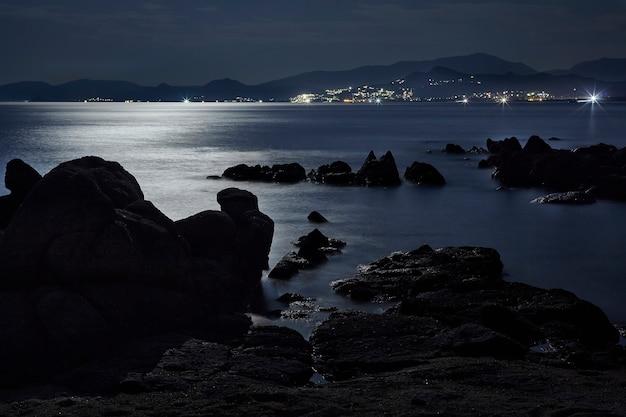 反射光に照らされたサルデーニャ南部のカポフェラートビーチの夜の海景
