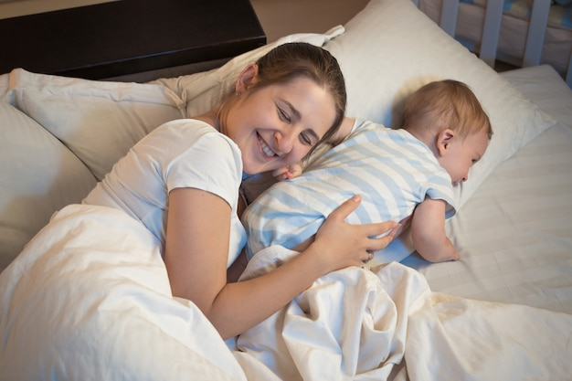 Night shot of happy smiling mother lying on bed with her little baby
