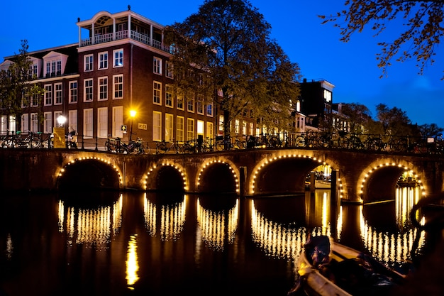 街の夜景、オランダ、アムステルダム運河の橋の上の多くの自転車