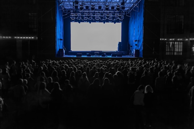 야간쇼 공연. 큰 흰색 스크린으로 현장 근처에서 많은 사람들이 야간 쇼를 기다리고 있습니다.