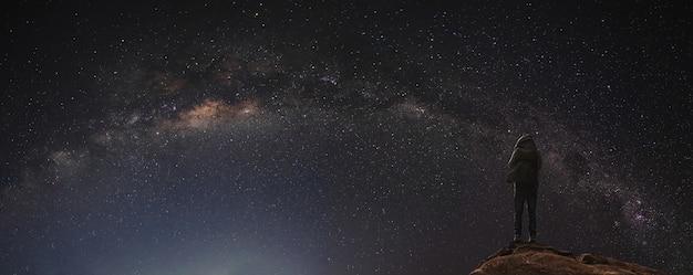 Ночное небо, полное звезд и млечного пути, с путешественником с рюкзаком, наслаждающимся красивым небом ночью