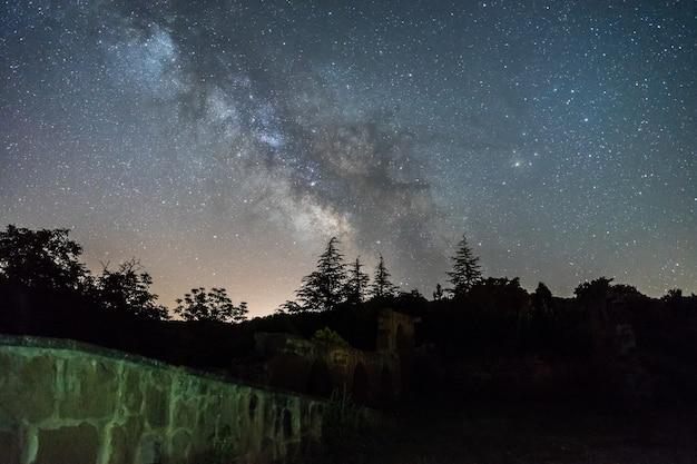 스페인의 숲과 유적 위의 은하수가있는 밤하늘