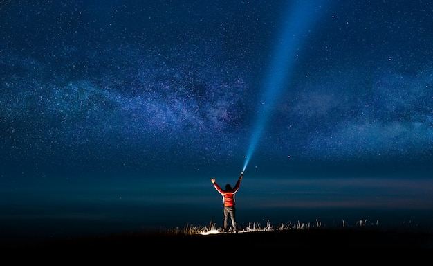 Night sky with  milky way and silhouette of a standing happy man with classic blue light.
