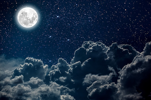 Night sky with stars and moon and clouds.